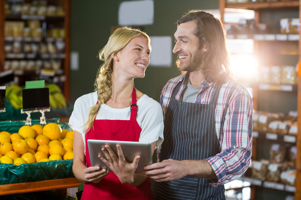 Smiling staffs using digital tablet in organic section of super market